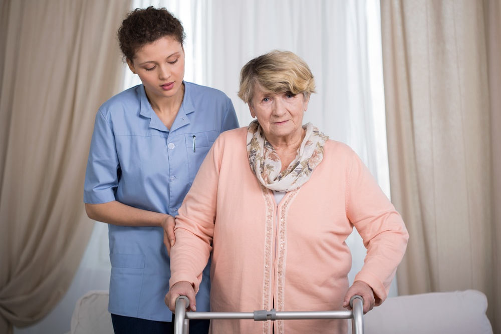 Aged disabled lady with walker and her helpful caregiver.jpeg