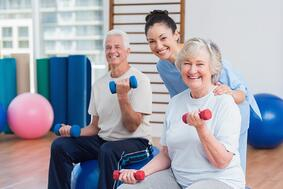 Portrait of happy female instructor with senior couple in gym