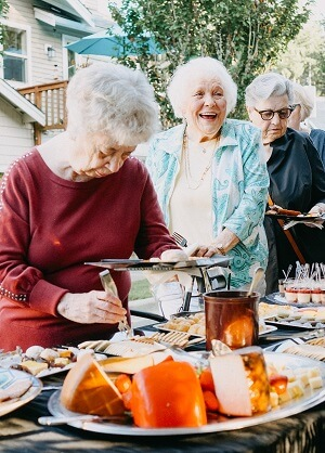 Village Green residents in a buffet line at Evening on the Green event in Federal Way, Washington