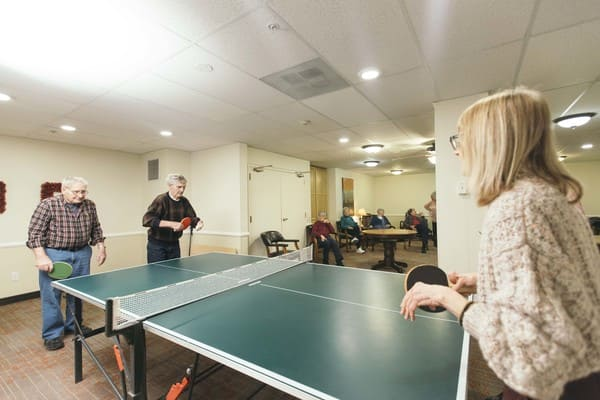Residents at Village Green Retirement Campus Participating in a Community Ping Pong Tournament-1